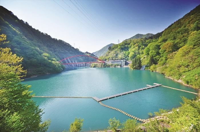 宇奈月大坝,整个水坝在鲜红拱桥和蓝绿河水的陪衬下,景色十分优美。